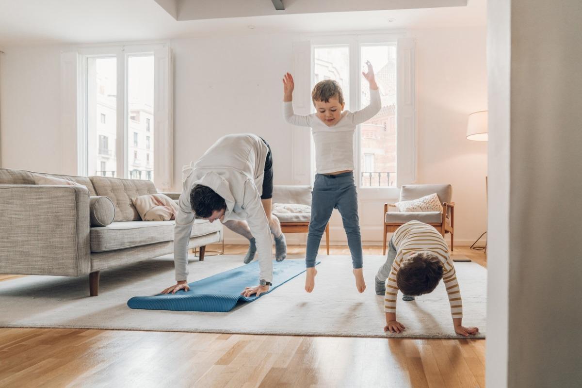 Padre con dos niños realizando ejercicio físico.